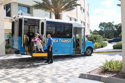 Space Coast Area Transit staff helping rider in wheelchair off bus