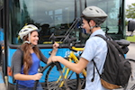 Students loading bike on bus bike rack