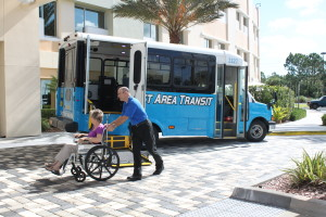 Paratransit driver pushing woman in wheelchair