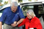 Volunteer helping elderly woman off van